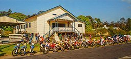 cream colored comunity hall with colorful motor bike s in front