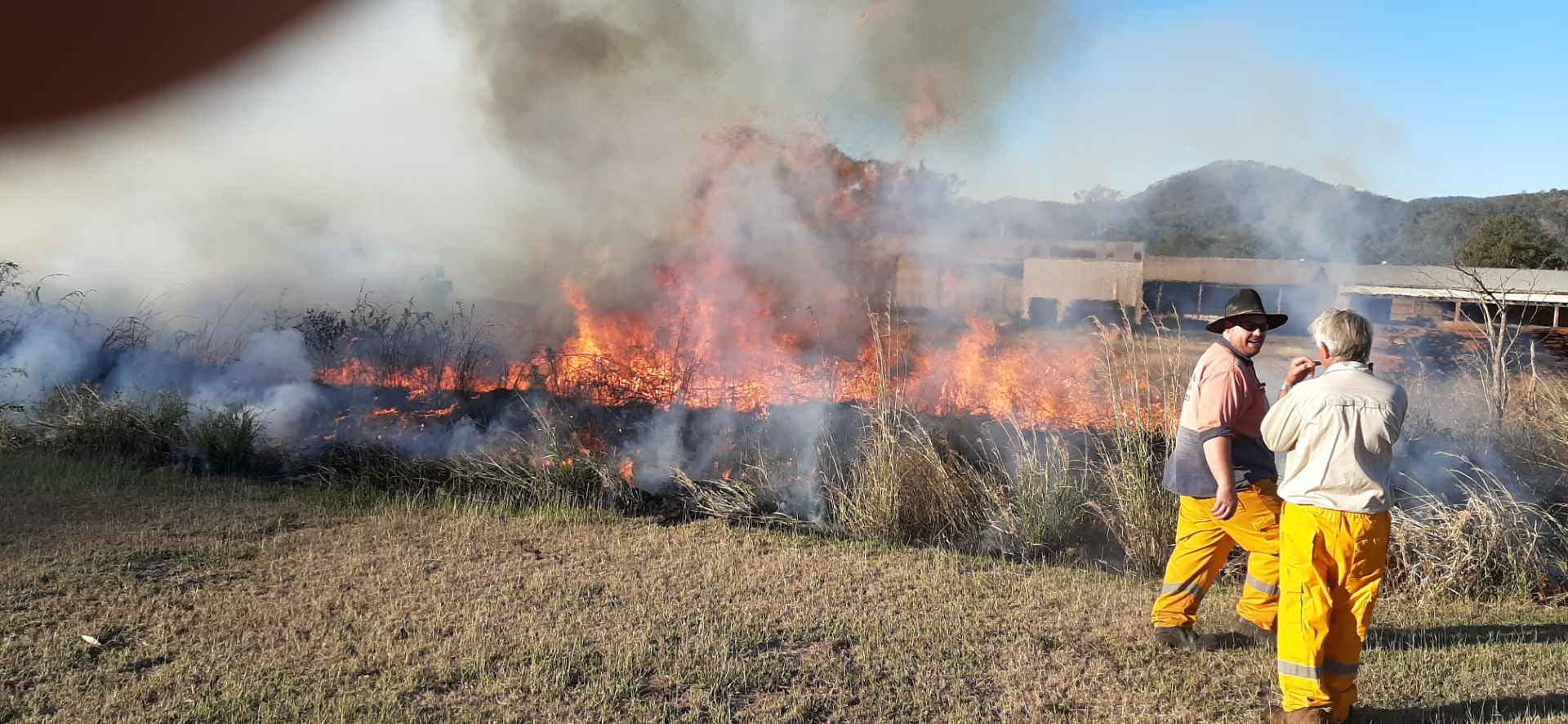 two fire fighters with fire burning grass