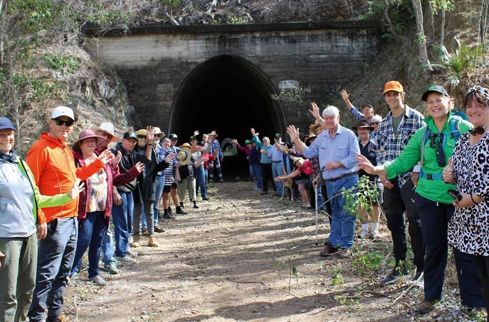 members and visitors at the mouth of a tunnel