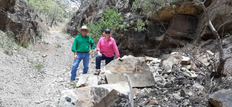 2 people standing on rock fall in a cutting