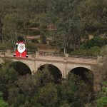 concrete arch bridge with santa and xmas trees